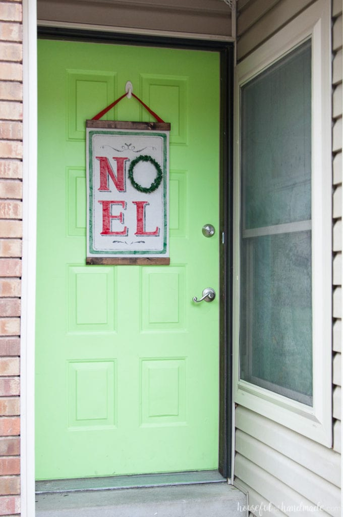 full view of green front door with vintage noel scroll