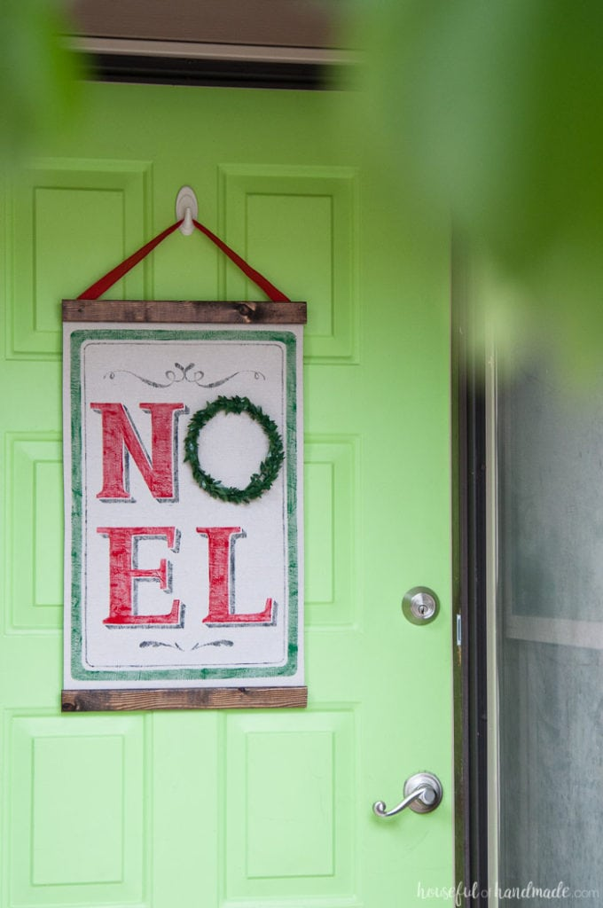 DIY vintage Christmas Noel scroll shown hanging on green door