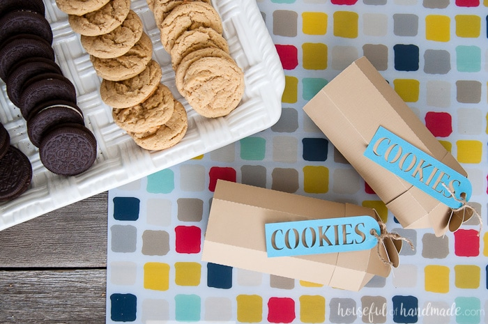 two printable paper cookie boxes laying horizontally on a table next to a tray of cookies