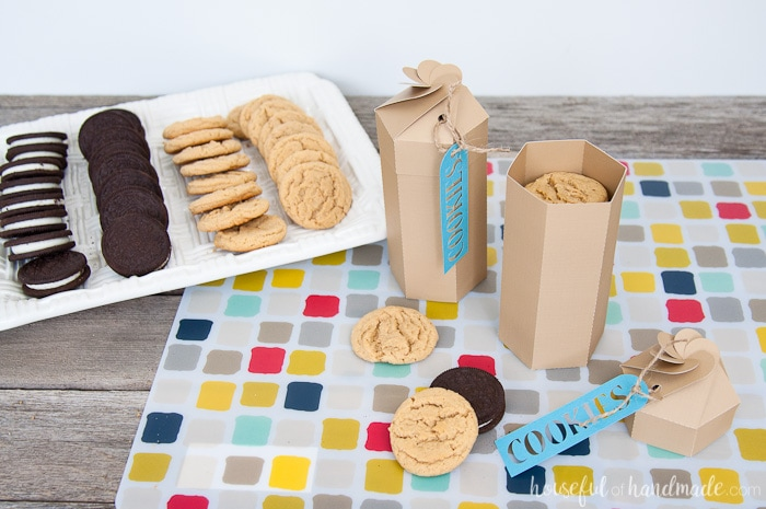 two open diy paper cookie boxes showing the cookies inside next to a tray of cookies