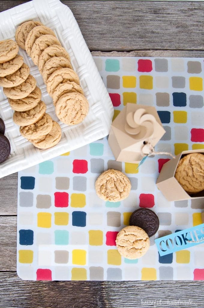over head view of two printable cookie boxes, one open, next to a tray of cookies
