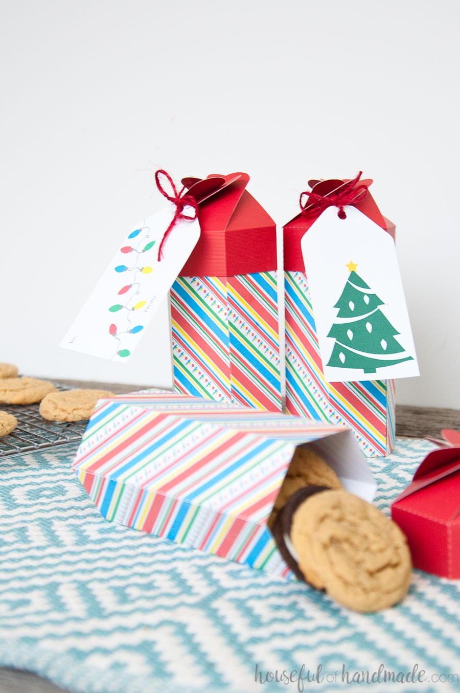 Three colorful tall Christmas cookie boxes, one tipped over, filled with a stack of cookies.