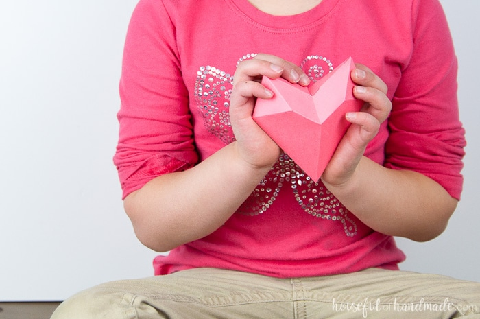 3D paper heart being held up against the chest where the heart is by a child.