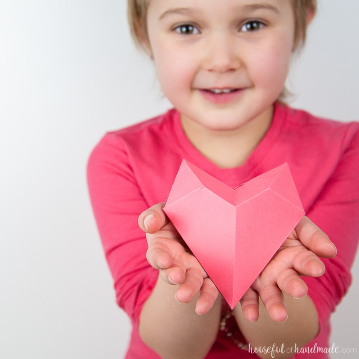 Little girl holding a 3D paper heart made out of pink cardstock in her hands.