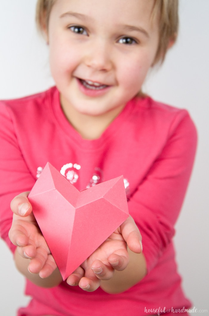 little girl holding a 3d pink heart valentne