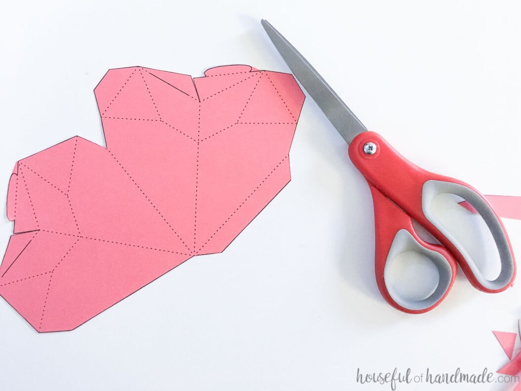 3D heart template cut out of pink cardstock on a craft table with a pair of scissors.