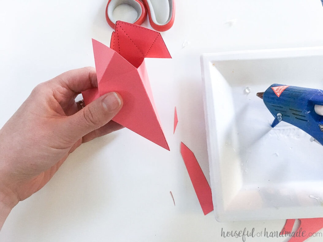 Glueing the side flap of the paper heart with hot glue.