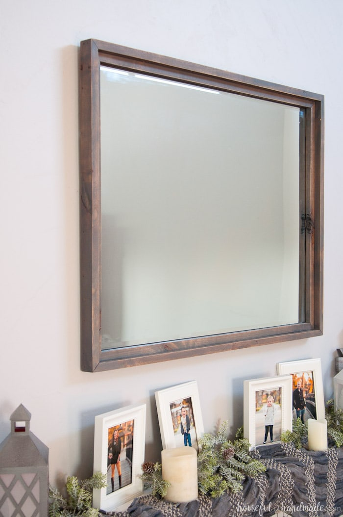 Gray stained frame around large beveled mirror over mantel.