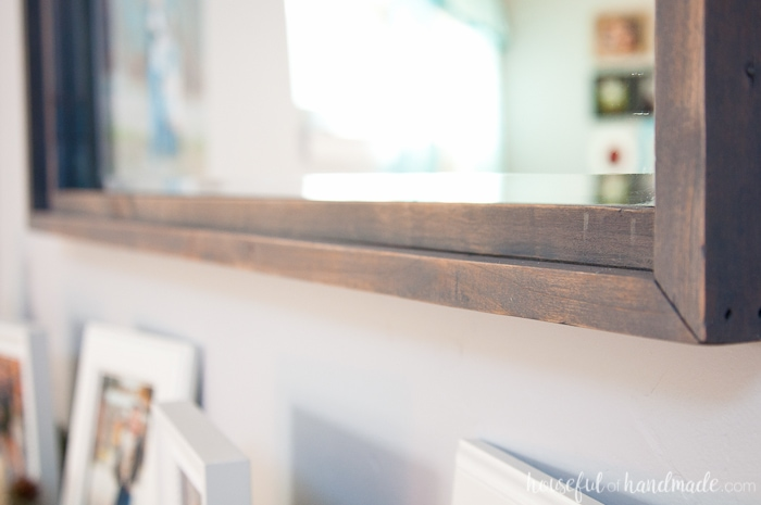 Large decorative mirrors are so expensive but make such an impact on your home decor. See how easy it is to make a DIY rustic mirror from just a few boards and an inexpensive mirror. I actually made it completely out of wood scraps. | Housefulofhandmade.com