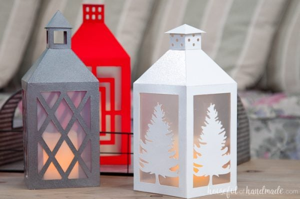 Paper Christmas decor of 3 paper lanterns with different colors and window designs.