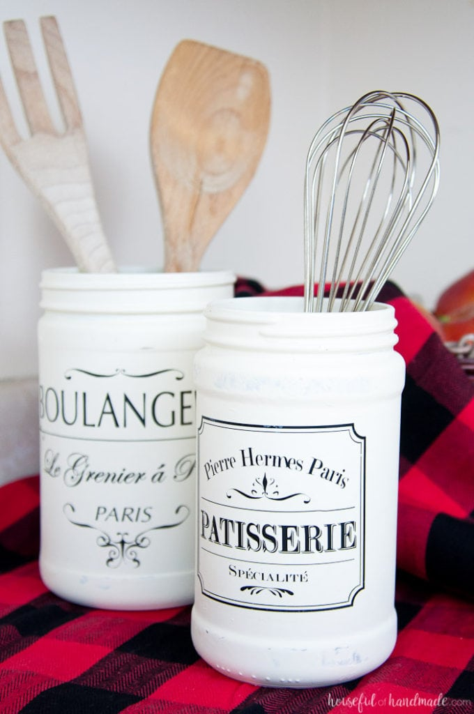 Two old jars refinished with white paint and french quotes shown as kitchen jars.
