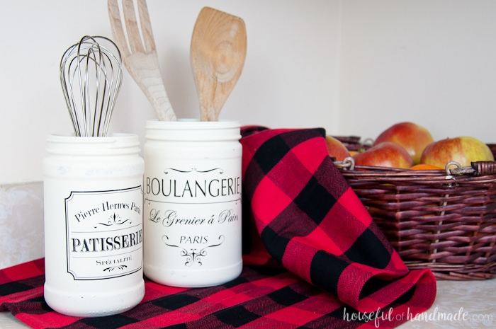 set of two white painted bakery jars shown on buffalo plaid next to basket.