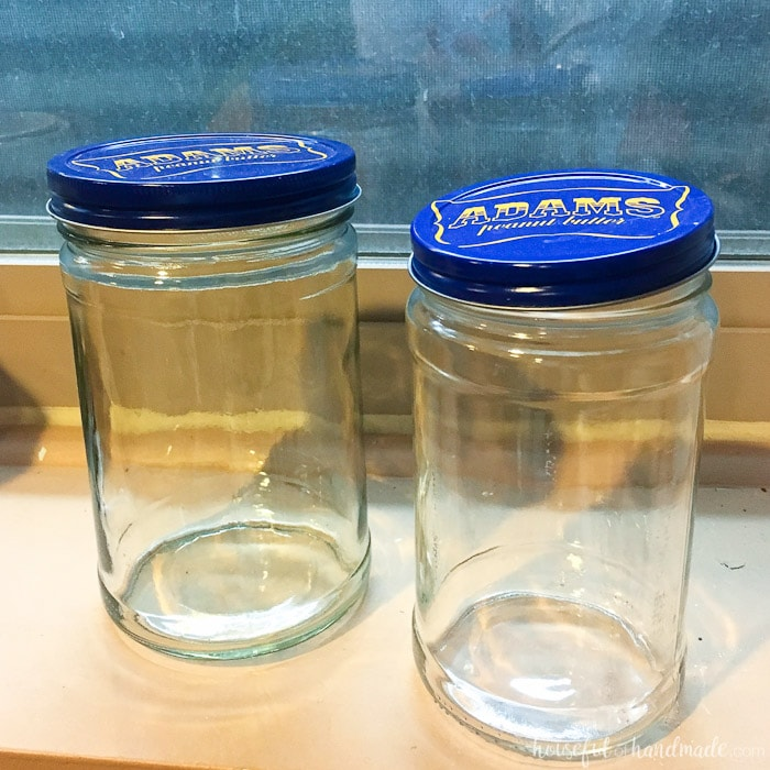 set of two glass peanut butter jars with blue lids.