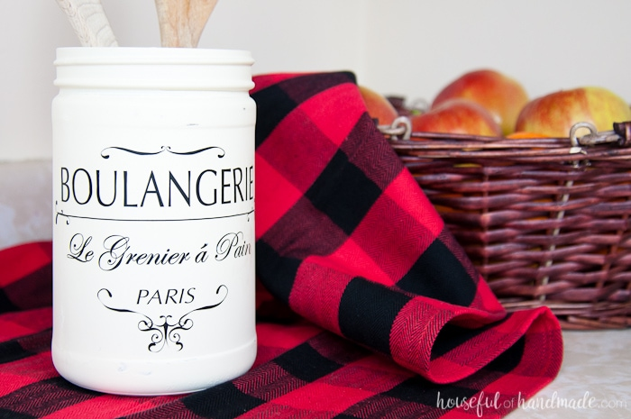 white painted jar with french quote shown on red buffalo plaid next to basket.