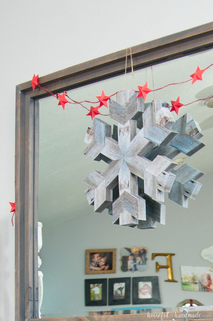 3D paper snowflake made to look like barn wood hanging on a mirror for the perfect paper Christmas decor.