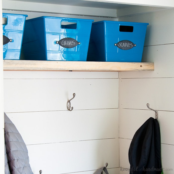 Blue dollar store bins in the mudroom with chalkboard labels on the front to keep things organized.