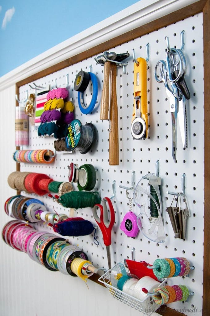 Create the perfect place to organize your most used supplies! Learn how to hang pegboard so it is removable if needed. Housefulofhandmade.com   Craft organization ideas   Craft room remodel   Pegboard organization   $100 Room Challenge   Easy woodworking   Easy building plans   Free Building plans
