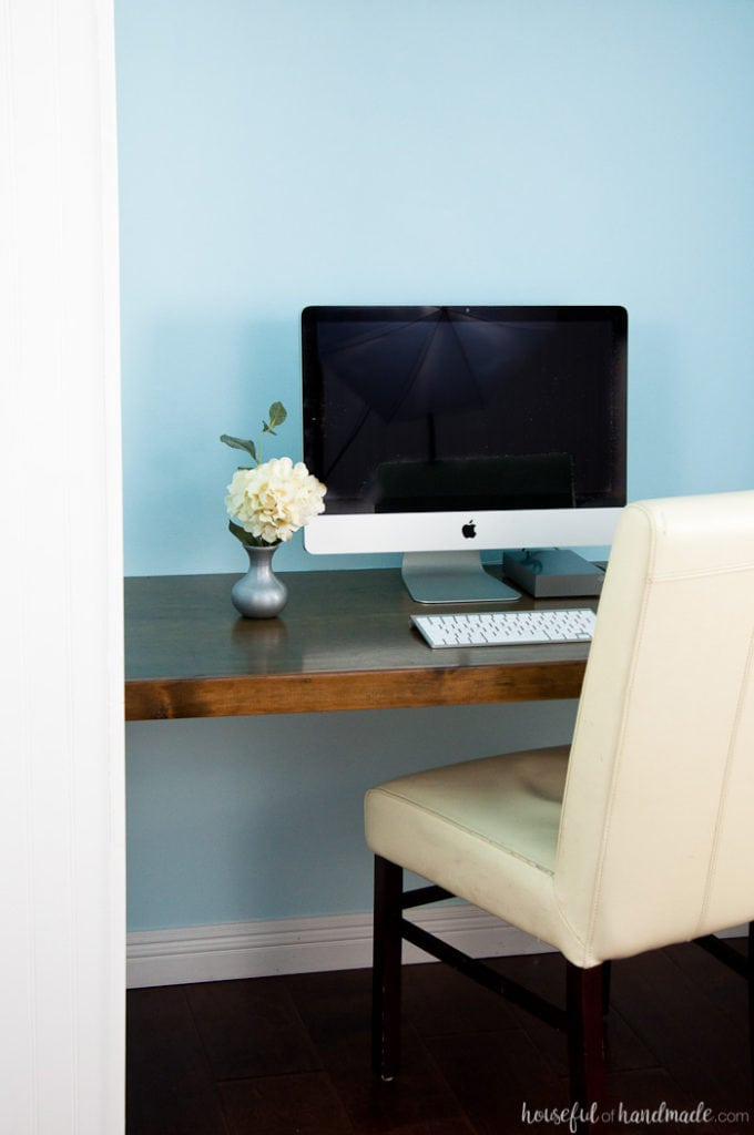 finished office in a closet shown with blue painted walls, wood stained desk top and office chair