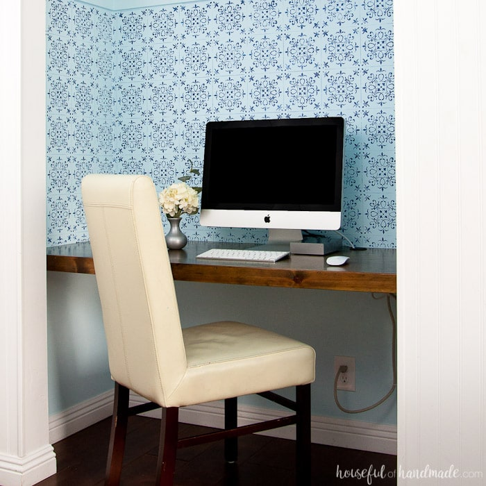 office in closet shown with wood desk, office chair, blue wall paper and office computer