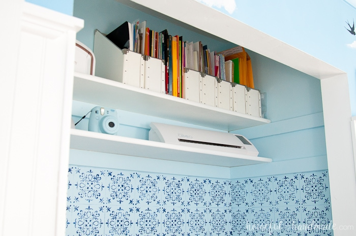 Storage shelves in office closet with blue wall paper and blue painted walls