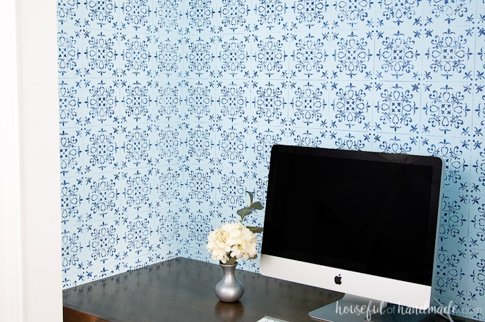 DIY desk shown in closet with blue pattern wall paper and white apple computer on wood desk