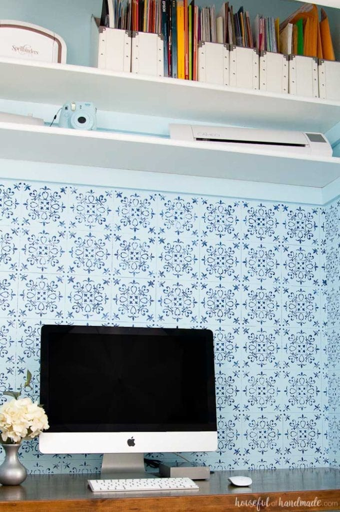 office desk built in closet with wood desk top, two storage shelves and blue patterned wall paper