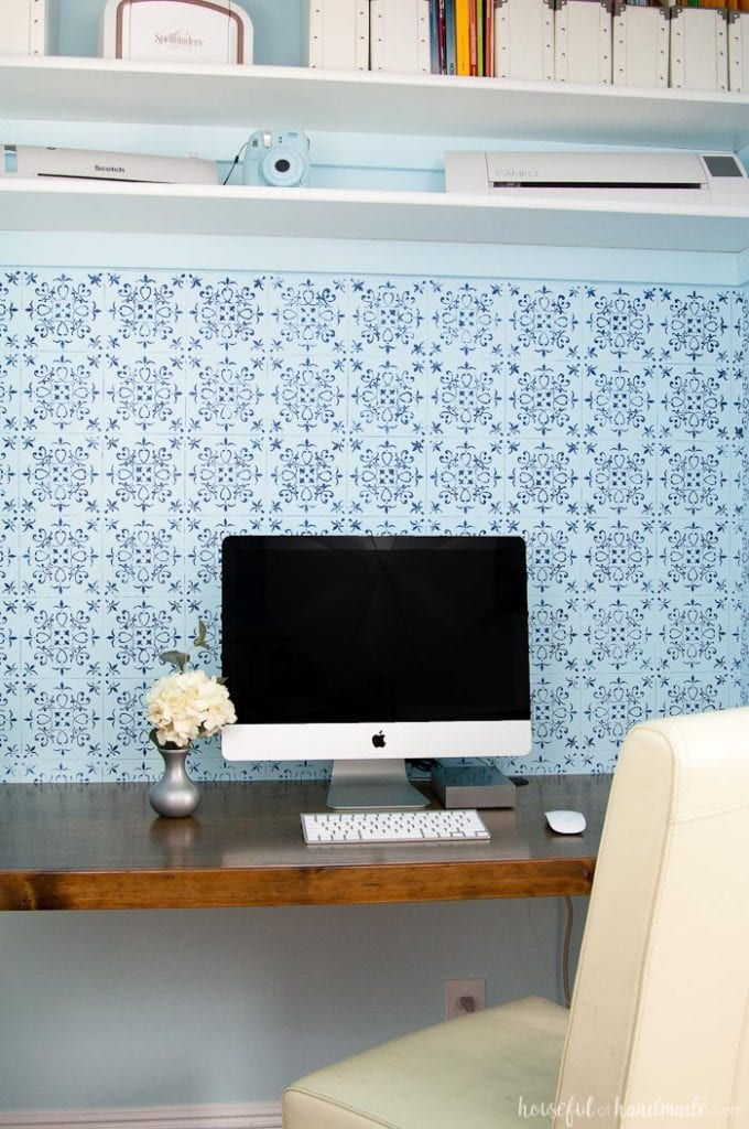 DIY desk built in a closet with wood desk top, blue wall paper for backsplash shown with white apple computer and desk chair.