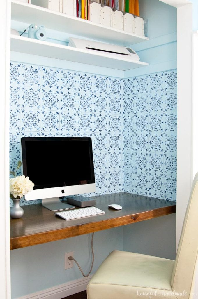 wood desk built in a closet with two shelves, desk chair and computer with blue patterned wall paper