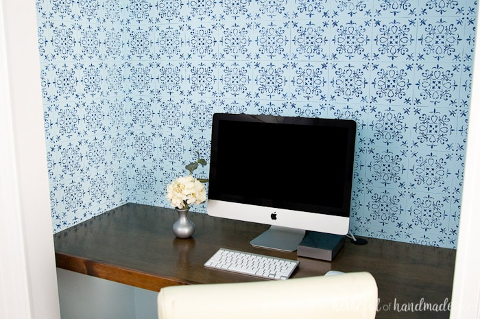 office in closet shown with finished blue patterned wall paper, wood desk top and computer