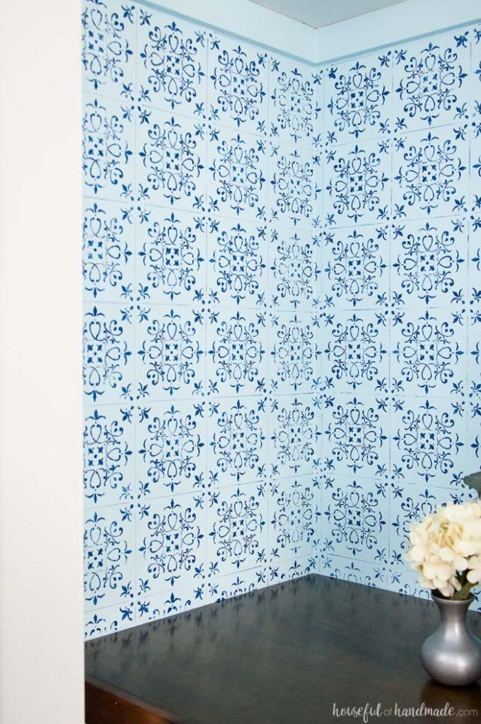 inside of office closet with wood desk and blue wall paper with vase of white flowers