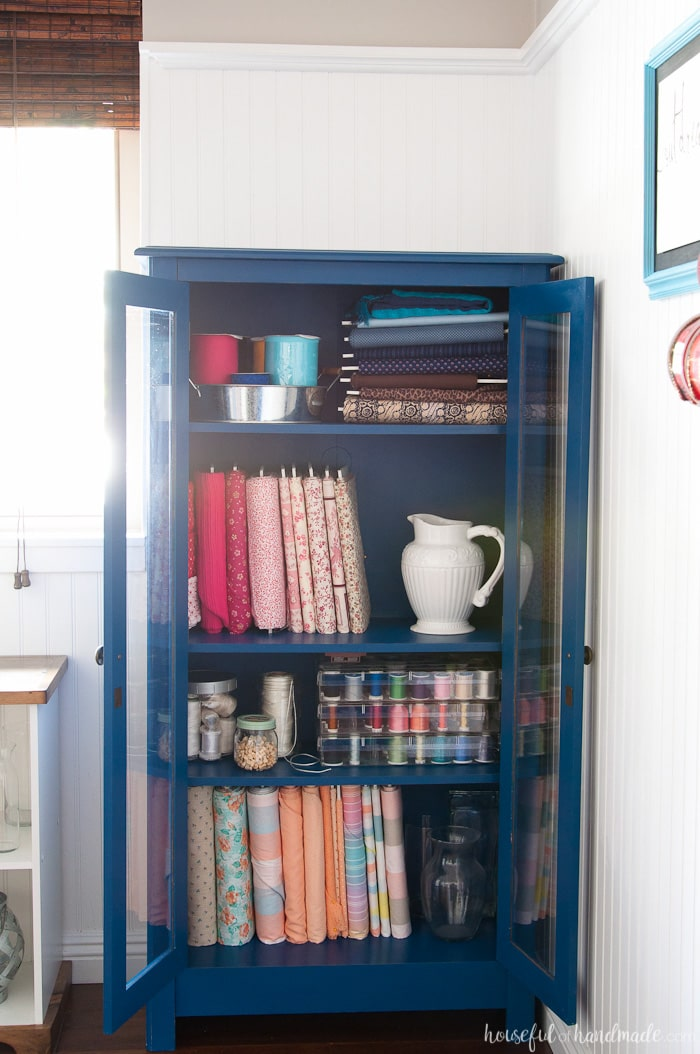 Cabinet in craft room with fabrics and sewing supple organized in it.