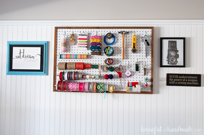 Framed pegboard storage for craft supplies on the wall.