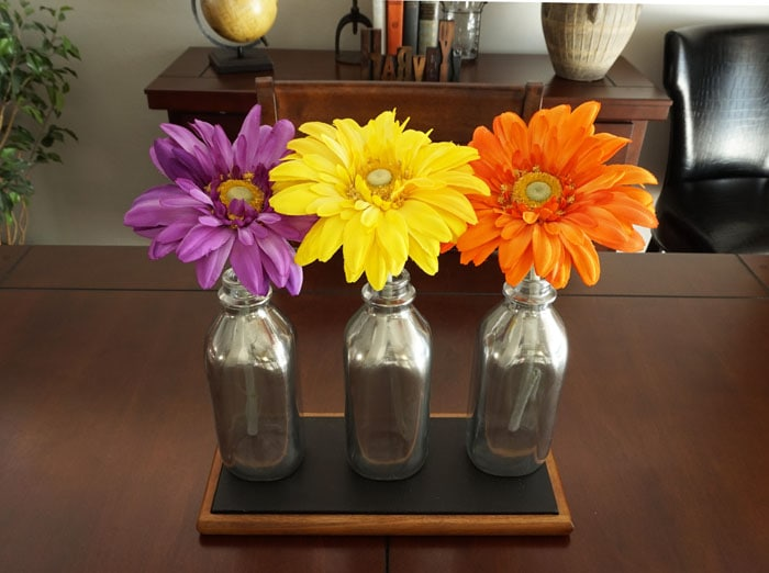 Ways to Upcycle Glass Jars & Bottles: Mirrored Milk Bottle Centerpiece from Small Home Soul.