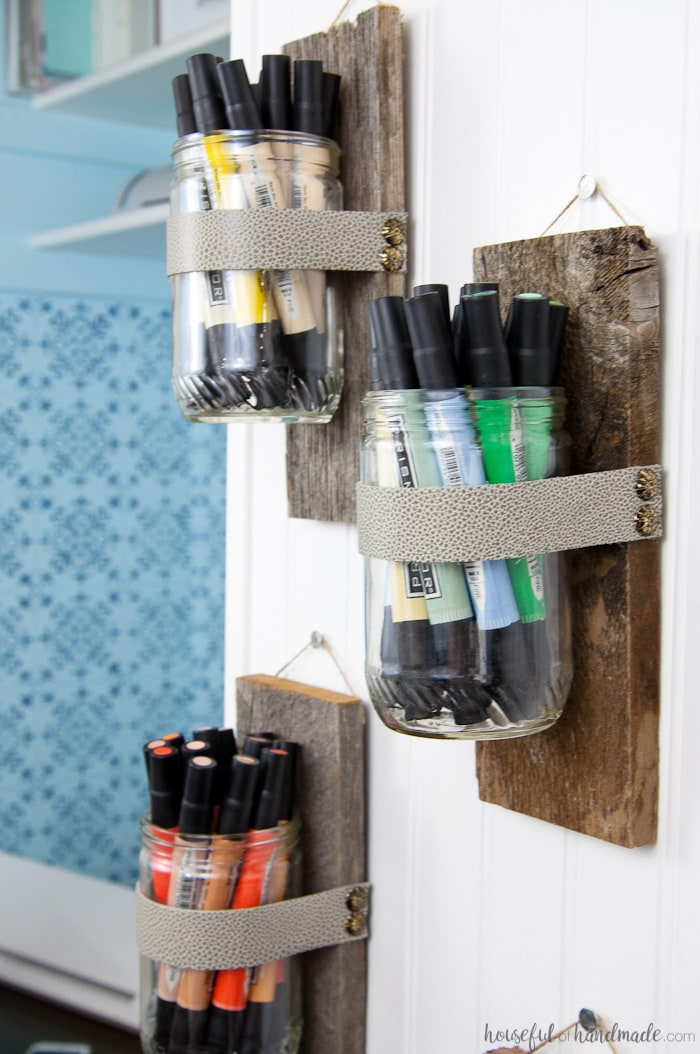 Use these amazing DIYs to Organize your home this year. Upcycle old peanut butter jars into DIY wall vases for the perfect farmhouse decor. Use your wall vases to display art supplies, flowers or herbs. Tutorial from Housefulofhandmade.com | Farmhouse Wall Decor | Rustic Wall Vase | 10 minute Crafts | Reclaimed Wood | Upcycle Ideas | Farmhouse Decor Tutorial | Craft Supply Organization Ideas