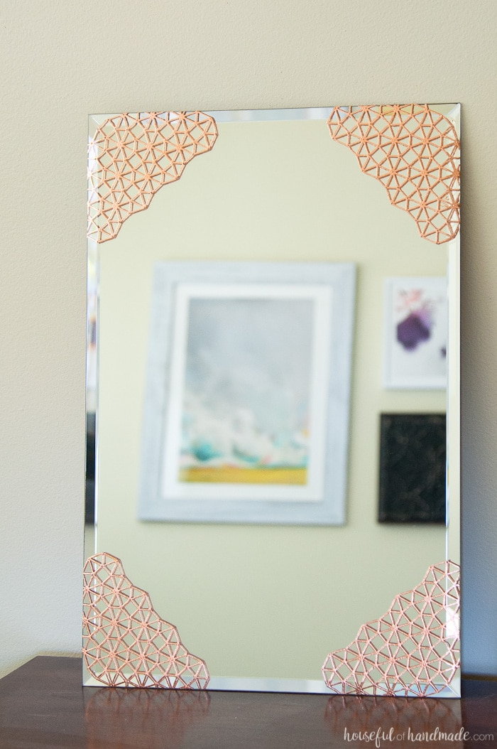 Add beautiful metal accents to a plain mirror. This DIY copper mirror is the perfect accent mirror for any room. Housefulofhandmade.com | DIY Home Decor | DIY Mirror Ideas | Copper Home Accents | Spellbinders
