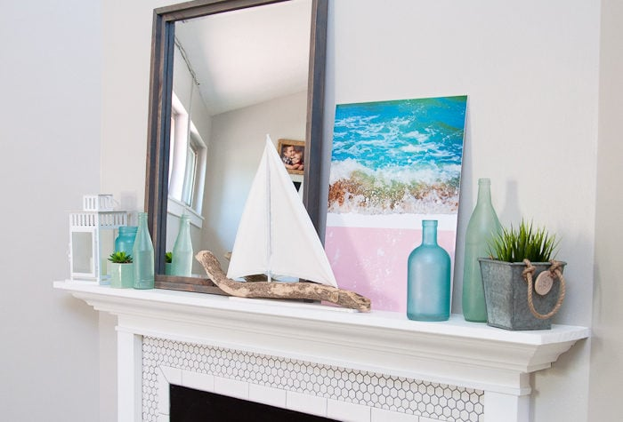 "Create the perfect summer mantel decor with ""found"" beach objects. A DIY driftwood sailboat and mirror are the jumping off point for this soft beach house inspired summer mantel for the Decorate Your Mantel Series. Housefulofhandmade.com 