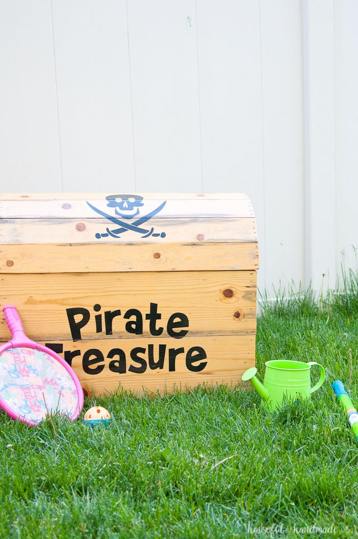 DIY treasure chest toy box shown on grass with kids toys.