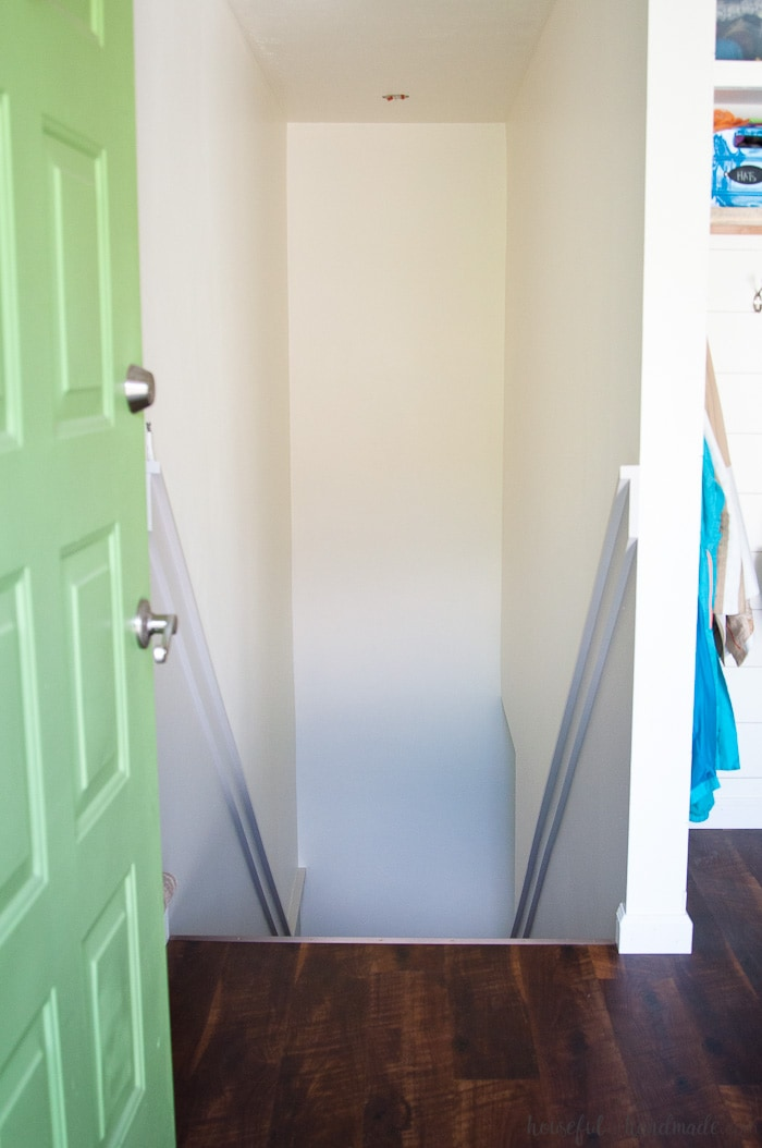 image of painted staircase with green door and hardwood floors