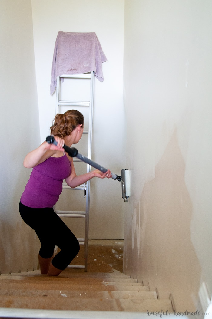 painting down staircase with ez twist paint roller