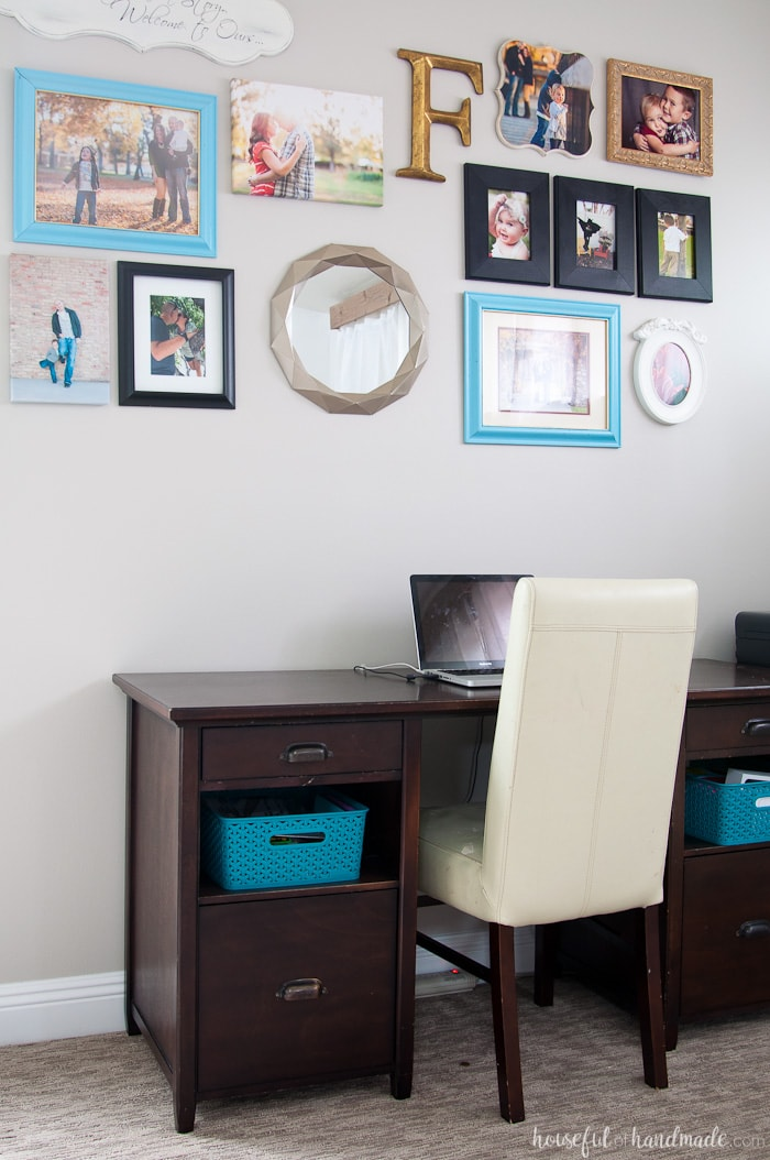 Desk against a wall with picture frames in colors that go with perfect greige
