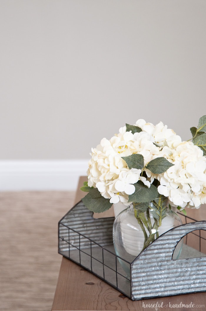 Flower arrangement in room with griege wall.