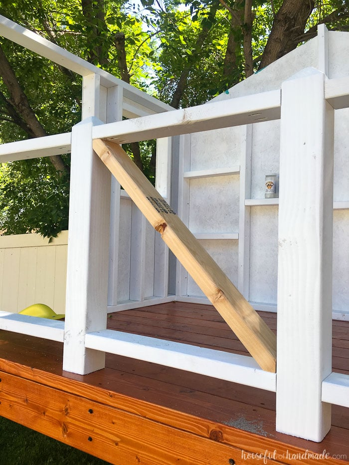 Our DIY Playhouse is coming along! This week we tackled the railing. The beautiful X railing is perfect for the cute cottage playhouse. See how we are building the playhouse step-by-step including free build plans and time/cost breakdown. Housefulofhandmade.com | DIY Playhouse | Playhouse Build Plans | DIY Swing Set | How to Build a Playhouse | DIY Sandbox