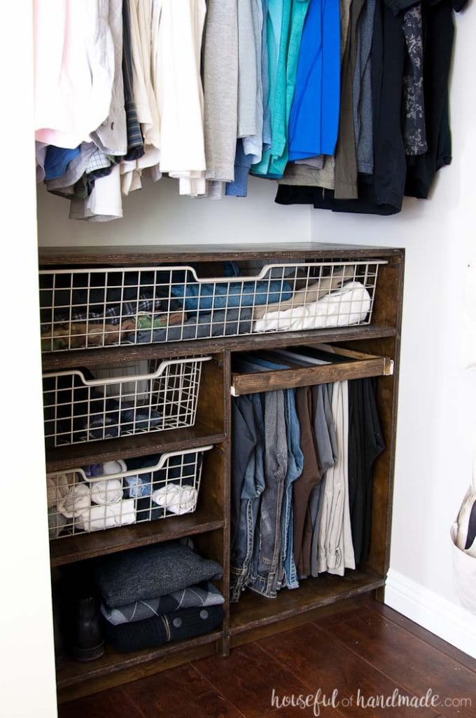 DIY closet organization system with baskets and shelves made from plywood.