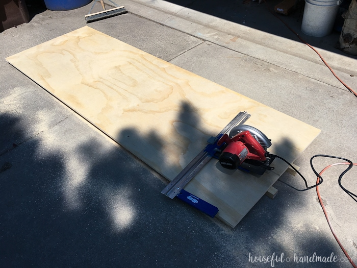 """Cutting the plywood into 15"""" wide strips with a circular saw and guide."""