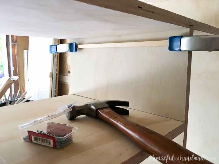 Showing the square dowel clamped and nailed inside the closet cubby.