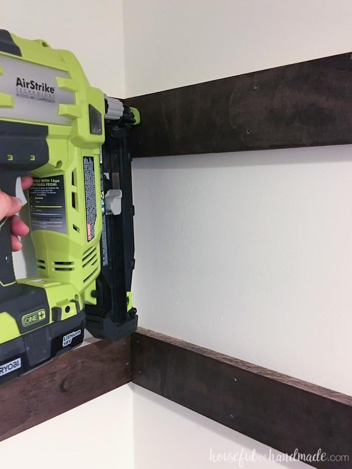 Nailing the shelf supports into the closet with a Ryobi nail gun.
