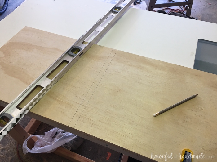 Groove for the cabinet shelves drawn on the plywood and a level next to it.