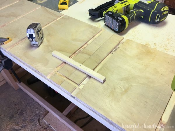 A scrap piece of wood nailed on the board to router the groove for the toe kick.