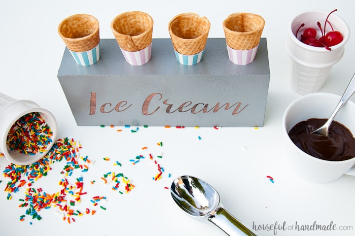 DIY farmhouse ice cream cone holder with empty cones surrounded by sprinkles, hot fudge, and cherries.