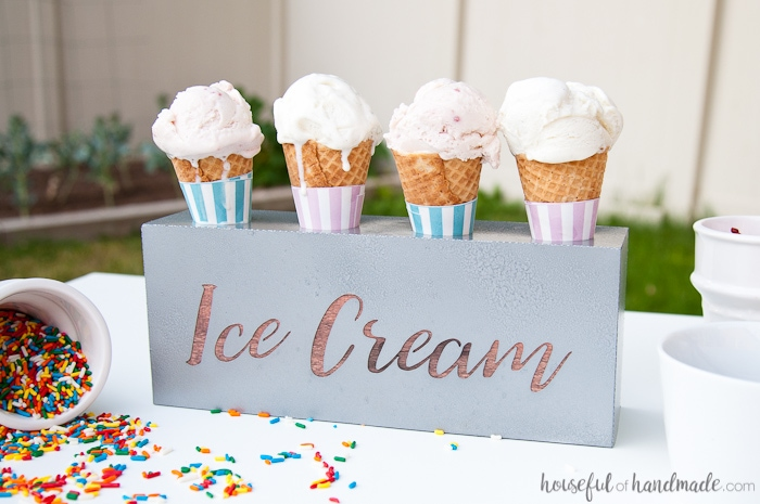 DIY farmhouse ice cream cone holder on an outdoor table.  Sprinkles container on its side with two other white containers